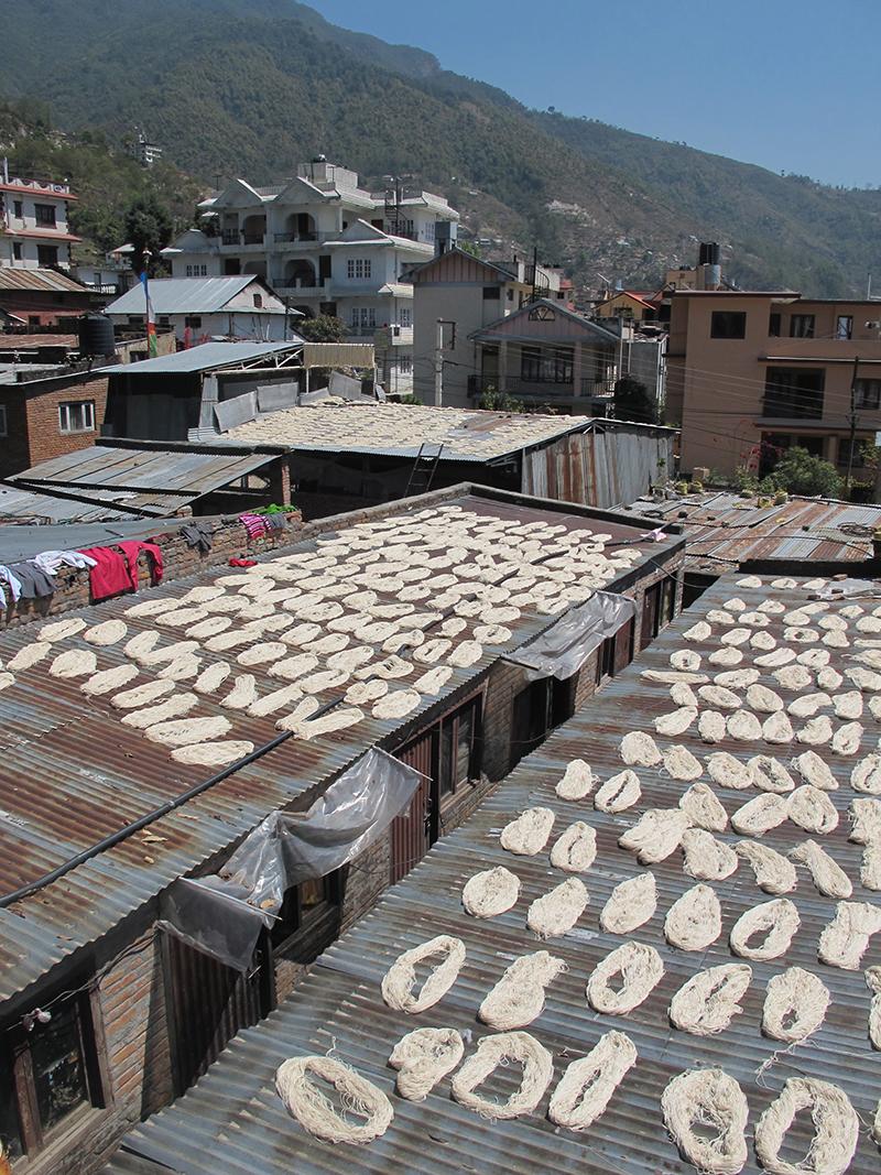 Hanks of wool dry on rooftops.
