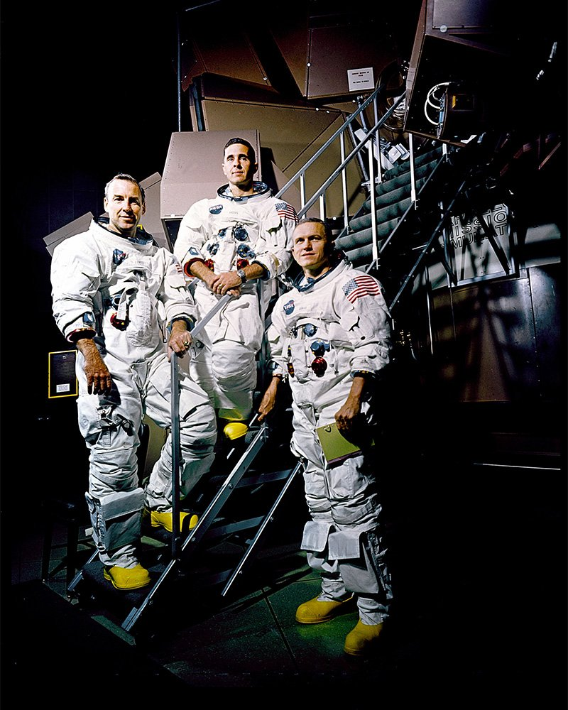 Apollo 8's crew members photographed posing on a Kennedy Space Center simulator in their spacesuits. From left are James A. Lovell Jr., William A. Anders, and Frank Borman