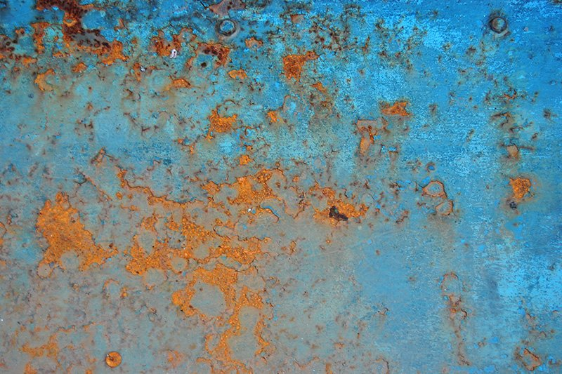 The pattern on a rusted, blue fence © MICROmacro