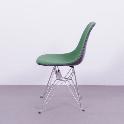 black fiberglass chair with green upholstery by charles ray eames