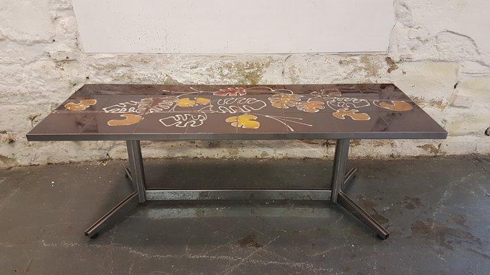 Tavolino con piastrelle e disegno di foglie marroni e arancioni