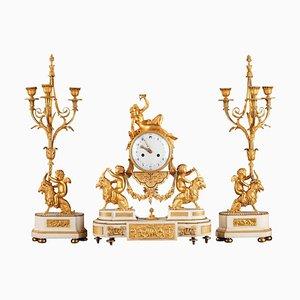 Reloj y candelabros Luis XVI de ormolú y mármol. Juego de 3