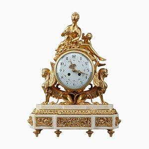 Reloj estilo Luis XVI de bronce dorado y mármol blanco