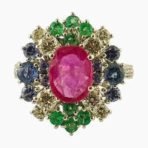 Anillo central de rubí, diamante, esmeralda, zafiro azul y oro blanco
