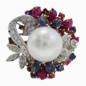 Anello con diamanti, rubini, zaffiri blu, perle e oro
