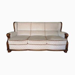 Sofá tapizado en blanco y butaca a juego