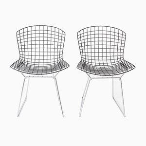 Sillas Wire vintage con asientos negros y base cromada de Harry Bertoia para Knoll. Juego de 2