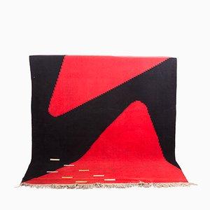 Alfombra checa vintage con motivos geométricos en rojo y negro
