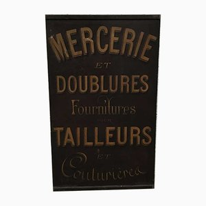 Cartel Mercerie de metal publicitando una sastrería, 1923