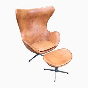 Egg chair in pelle color cognac con poggiapiedi di Arne Jacobsen per Fritz Hansen, anni '60