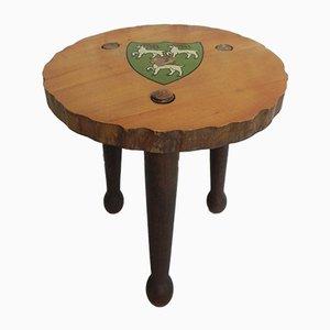 Taburete de madera con trípode decorado con un escudo, años 60