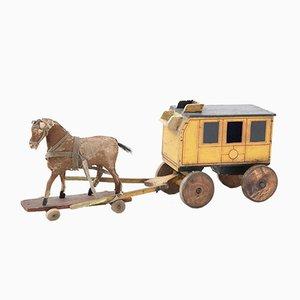 Antikes Postkutsche.Spielzeug mit Pferdefellbezug