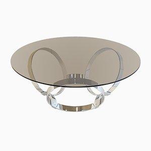 Mesa de centro era espacial de vidrio y pie con tres anillas de metal cromado, años 70