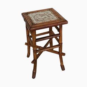 Mesa auxiliar antigua de bambú con tablero de baldosa