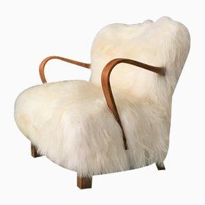 Butaca modelo WH237 de madera curvada con piel de oveja blanca de Jindřich Halabala, años 40