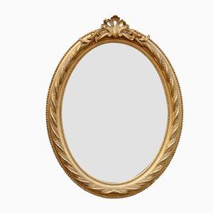 Espejo antiguo oval dorado con ornamentación en la parte superior