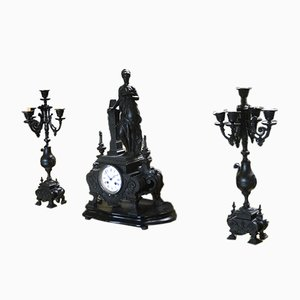 Reloj antiguo de hierro fundido con dos candelabros