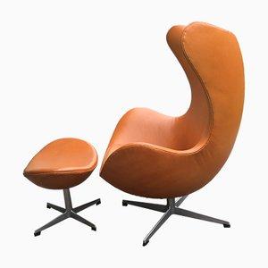 Egg Chair in pelle marrone chiara con poggiapiedi di Arne Jacobsen per Fritz Hansen, 1967