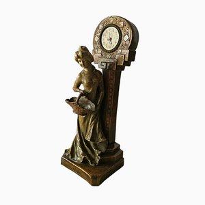 Statuetta Art Nouveau di donna con orologio in terracotta, inizio XX secolo
