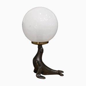 Figura de foca Art Déco de bronce con globo de vidrio
