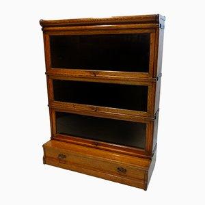 Antikes elastisches Bücherregal aus Messing, Glas & Leinen von Globe Wernicke