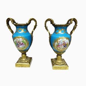 Jarrones franceses antiguos de bronce dorado y porcelana. Juego de 2