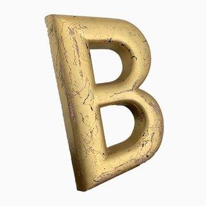 Letra B inglesa industrial vintage de cemento pintado en dorado