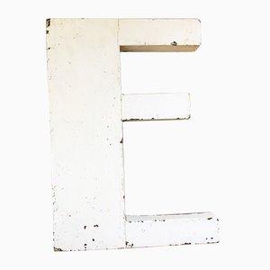 Cartel de letra E blanca de madera, años 30