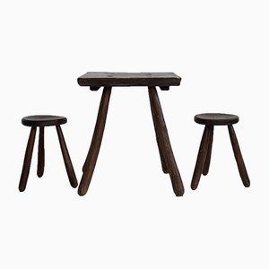 Conjunto de mesa de trabajo y taburetes trípodes rústicos de madera, años 50