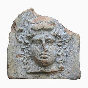 Antefijo de terracota antiguo griego en forma de cabeza de Artemis Bendis