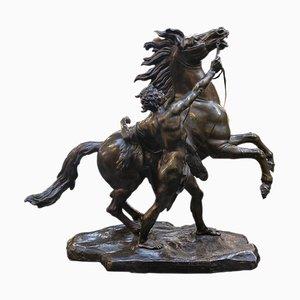 Skulptur aus Bronze stellt einen Mann dar, der ein Pferd zähmt