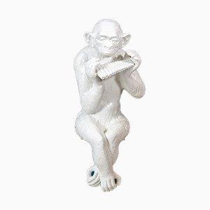 Großer sitzender Schimpanse spielt die Panflöte, 1974