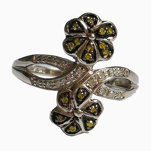 Silberner Ring mit floralen Motiven und grünen Rauten