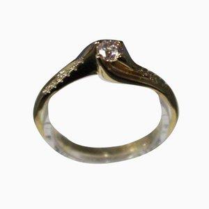 Anello in oro 14 kt con brillante 0,30 kt e 12 piccoli diamanti per 1,12 kt