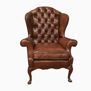 Antique English brown leather deep buttoned wing chair
