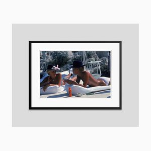 Sunbathing in Antibes Oversize C Print Framed in Black by Slim Aarons
