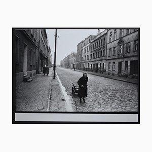 Anziana che cammina per strada con il suo carretto di Rolf Gillhausen, anni '40