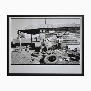 Uomo dell'area Mississippi seduto di fronte alla sua capanna di Rolf Gillhausen, Stati Uniti, anni '60