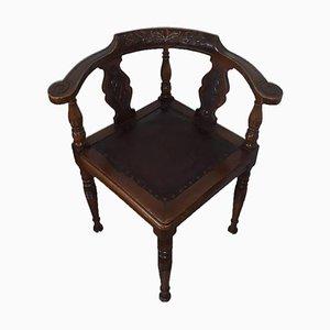 Antiker Stuhl aus dunklem Holz mit floralen Schnitzereien