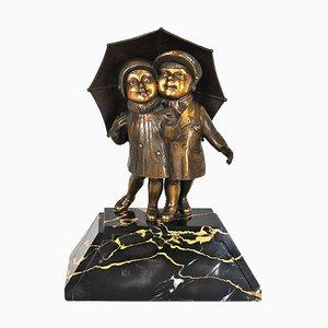 Guyot G, Art-Deco-Kinder unter einem Regenschirm, Bronzeskulptur