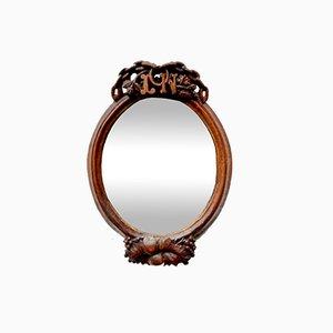 Specchio ovale antico con cornice in legno intagliato