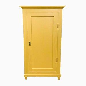 Armario antiguo con una puerta pintada en amarillo mostaza