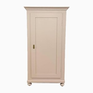 Armario antiguo con una puerta pintada en rosa pastel