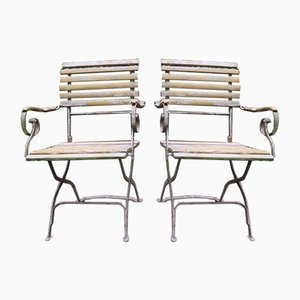 Sillas de jardín antiguas de hierro fundido patinado con brazos de desplazamiento. Juego de 2