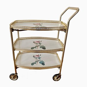 Bar Cart with a Golden Frame and White Trays with Rose Motif.