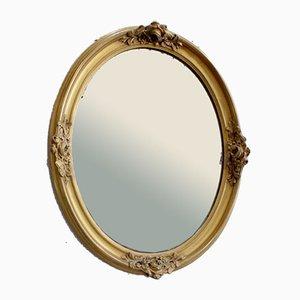 Espejo oval de finales del siglo XIX con marco de madera dorada