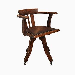 Sedia da ufficio da capitano antica girevole in pelle con rotelle e dettagli in ottone, inizio XX secolo