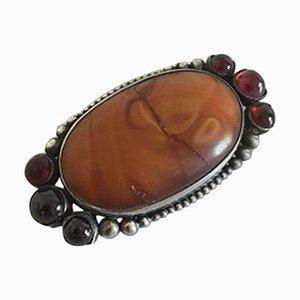 Broche plateado con piedras rojas y ámbar de Mogens Ballin