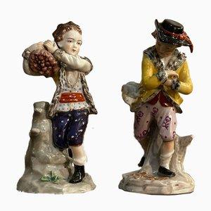 Niño de cerámica con sombrero y leña de Capodimonte. Juego de 2