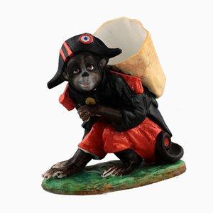 Portalápices de porcelana que representa a un mono disfrazado de Napoleón